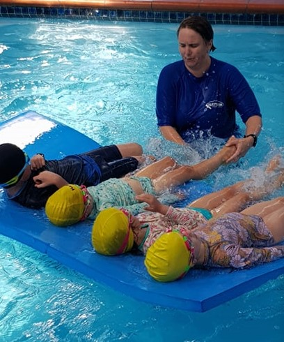 Phoenix Community House project co-ordinator Beth Rosser with swim class - kids kicking in the pool