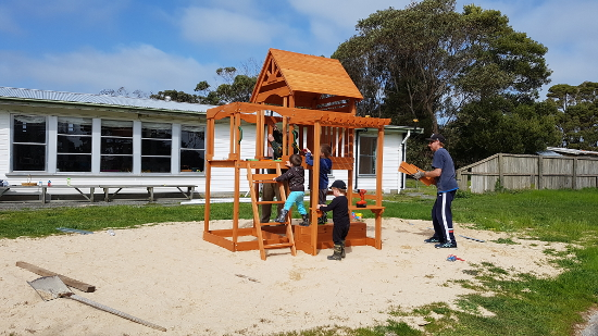 King Island Playground. Children playing whilst adult supervises.