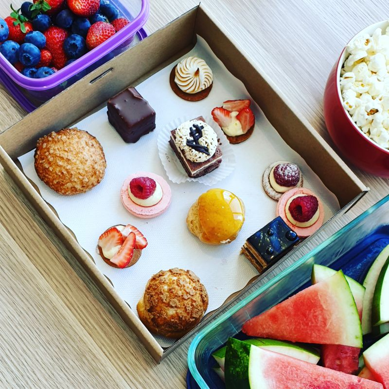 Selection of  deserts in a box, with fruit and popcorn in surrounding containers.