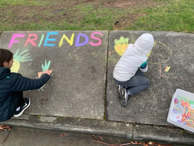 Two children write the word friends in chalk and draw fruit people in chalk messages on a foot path at Mt Nelson.