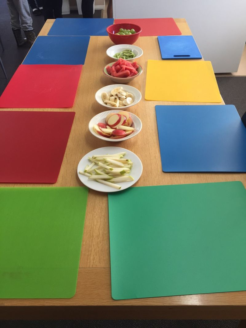 Table with brightly coloured placemats and healthy fruit and bowls of healthy fruit and vegetable in the centre of table.  Food Redi children's program designed cooking games around 'Superfood heroes', covering a different hero each week.