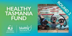 Children in water at the side of a pool smiling as they enjoy a learn to swim program funded through Healthy Tasmania.