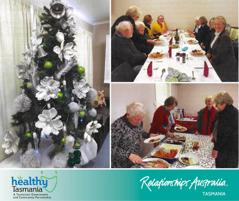 Older community members enjoying a Christmas meal with a large green and silver Christmas tree.