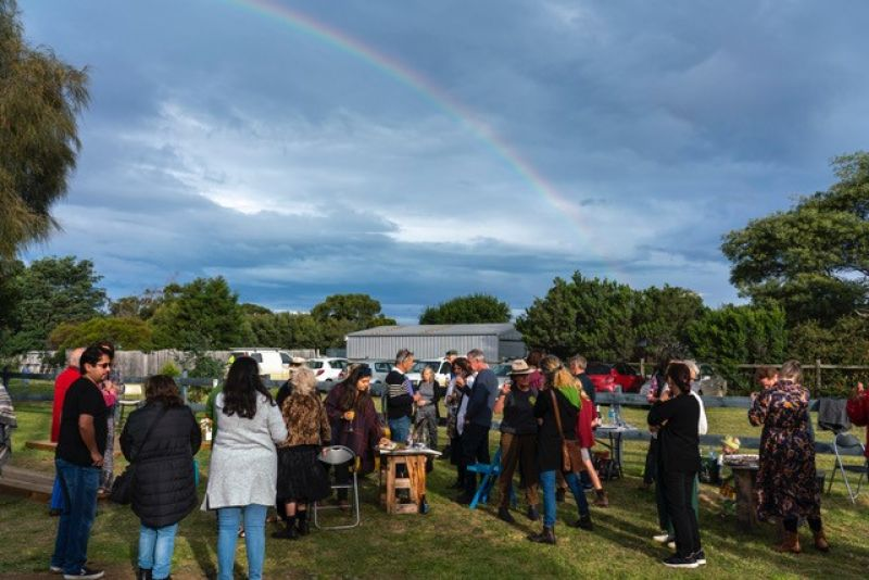 Neighbours gather to launch a new arts space on a sunny day in Marion Bay; a rainbow can be seen overhead.