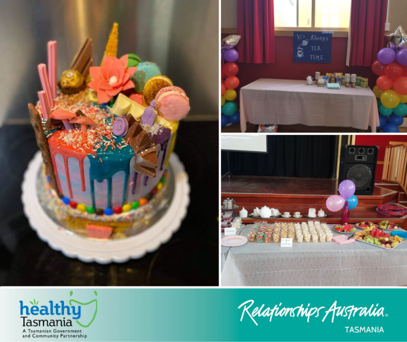 A very colourful and extravagant cake sits on table with healthy snacks and tea.