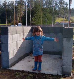 Child standing on a small cement pad, surrounded on three sides with a low brick wall.