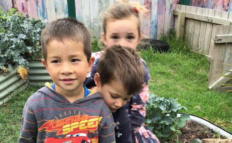 Three children standing in vegetable garden.